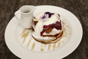 Pancakes with streaky bacon, grilled banana and maple syrup or Fresh banana, berry compote and natural yoghurt